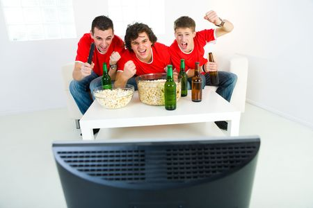 sport fan: Three happy men sitting on couch and watching sport on TV. Front view.
