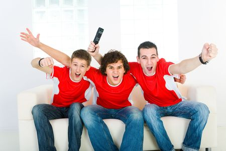 indoor soccer: Tres hombres emocionante sesi�n de sof� y viendo el deporte en la televisi�n.