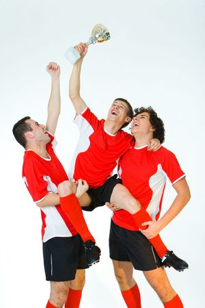 Group of happy men dressed sportswear holding a cup. Front view.