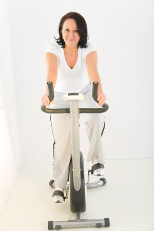 Elder woman exercising on spinning bike. Shes smiling and looking at camera. Front view.