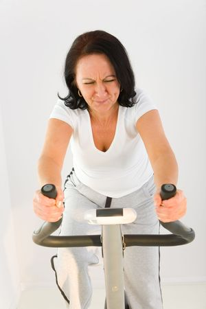 Elder woman exercising on spinning bike. She looks very tired. Front view.