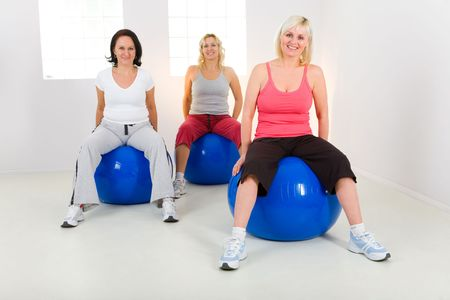 Women dresset sportswear working out on fitness ball. Theyre smiling and looking at camera. Front view. photo