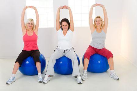 m�s viejo: Dresset las mujeres en la elaboraci�n de ropa deportiva fitness bal�n. Han planteado manos. Est�n sonriendo y mirando a c�mara. Vista frontal. Foto de archivo