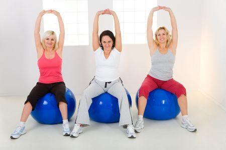 aging woman: Women dresset sportswear working out on fitness ball. They have raised hands. Theyre smiling and looking at camera. Front view. Stock Photo
