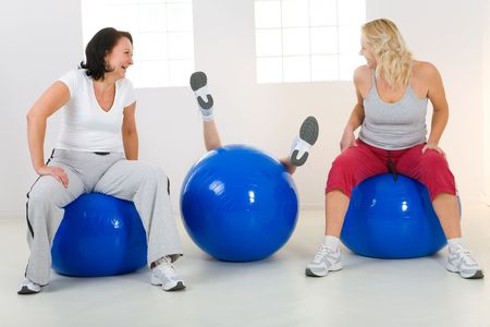 Women sitting on fitness balls. One of them slump from the ball. Two women laughing. Front view.