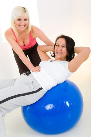 Elder woman dressed sportswear exercising abdominal muscles with her instructor. photo