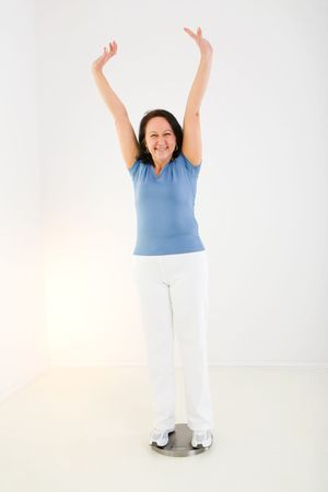 Woman dressed sportswear standing on bathroom scales. She looks very happy. Front view. Stock Photo
