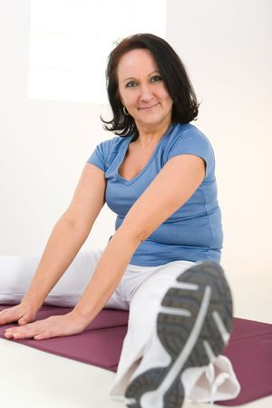 Senior woman stretching on mat. She's smiling and looking at camera. Low angle view. Banco de Imagens