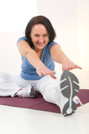 tiredness: Senior woman stretching on mat. Shes smiling and looking at camera. Stock Photo