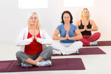 ejercicio aer�bico: Las mujeres mayores sentado con las piernas cruzadas sobre la estera y meditar