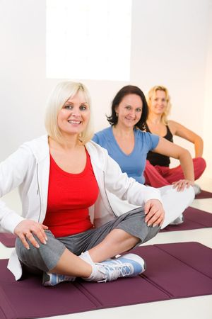 Elder women sitting cross-legged on mat and doing exercices. Theyre smiling and looking at camera.