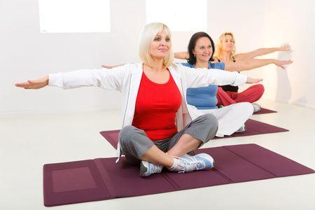 Elder women sitting cross-legged on mat and doing exercices.