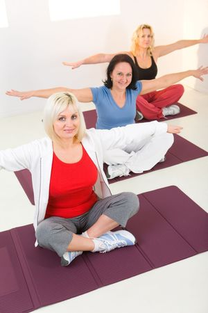 exercices: Elder women sitting cross-legged on mat and doing exercices. Theyre looking at camera. High angle view