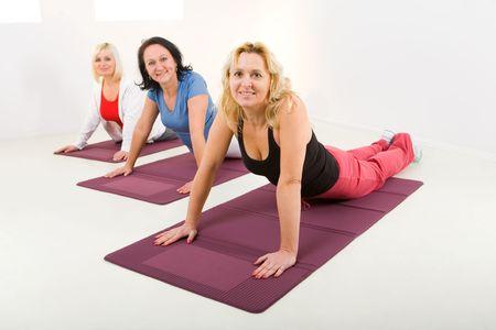 cansancio: Durante el ejercicio de las mujeres mayores en la estera. Est�n sonriendo y mirando a c�mara.