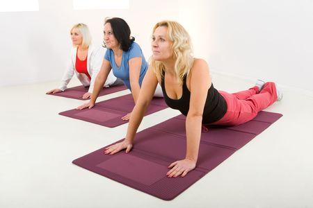 Elder women during exercising on mat.