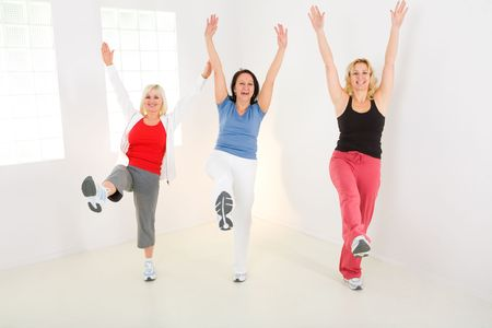 A group of exercising women. Theyre smiling and looking at camera.