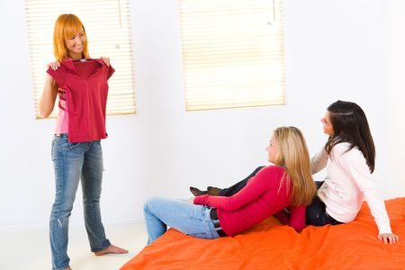 boast: Tre amiche in camera. Uno di loro mostrando nuove T-shirt. Due ragazze disteso sul letto.