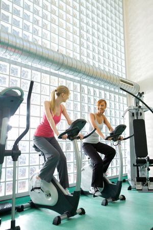 Young women working out  on spinning bike at gym.