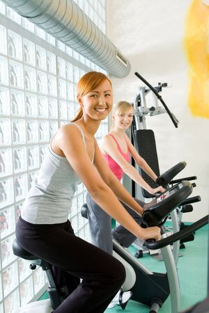 Young women during exercise on spinning bike at gym. Shes smiling and looking at camera. Side view. photo