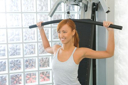 Happy woman working out arms muscles on exercise machine. photo