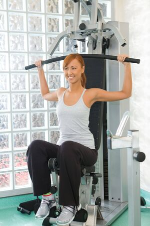 Happy woman working out arms muscles on exercise machine.