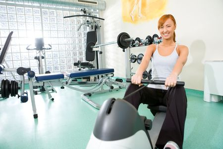 Young woman exercise on rowing machine at gym. Shes smiling and looking at camera.