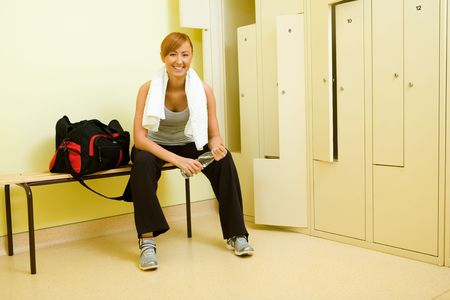 pew: Young woman with towel sitting on bench in locker room. Shes holding bottle of water. Stock Photo