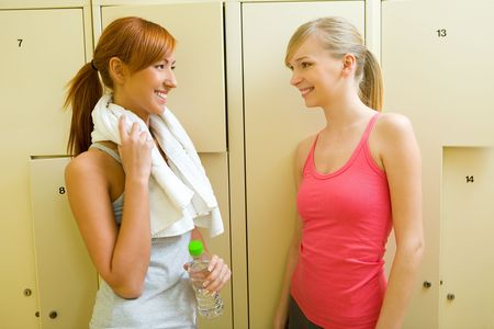 Two women stand in locker room and talking. One of them holding towel and bottle of water.