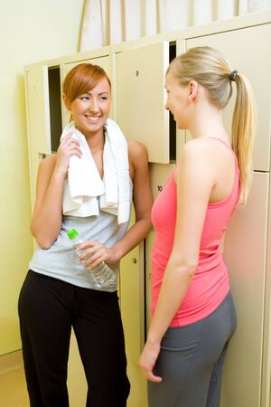 Two women stand in locker room and talking. One of them holding towel and bottle of water. photo