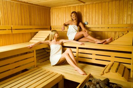 perspire: Two young woman in sauna. They looks happy.