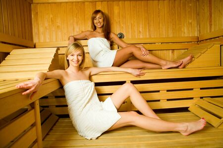 perspire: Two young women with towels sitting in sauna. Theyre looking at camera and smiling.