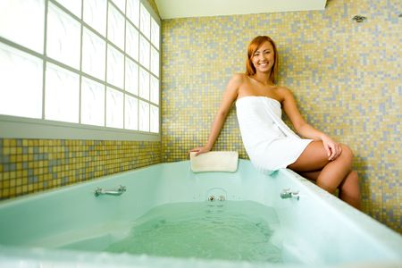 Young happy woman sitting on a bath tub in bathroom. photo