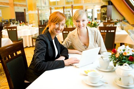 Two women sitting at table in restaurant. Theyre smiling and looking something on laptop.