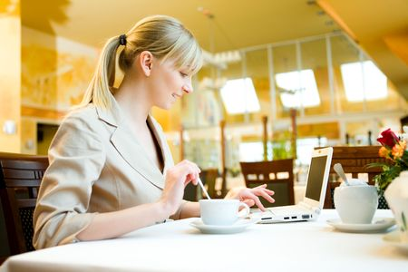 Young woman doing something in laptop. Shes sitting in restaurant.