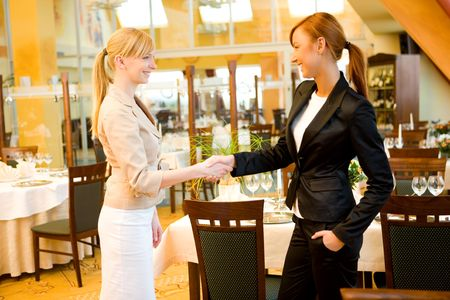 conclude: Two  businesswomen shake hands and conclude a deal. Theyre in restaurant.