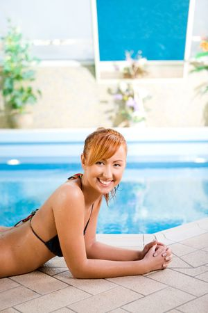 Sexy young woman lying by swimming pool. Shes smiling and looking at camera. photo
