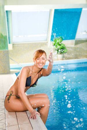 Happy young woman sitting on the edge of pool. She splashing. photo