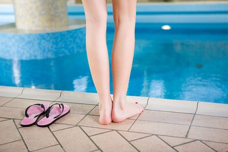 Woman standing on the edge of pool. View on legs. Stock Photo