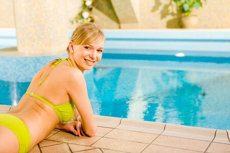 Happy blonde woman lying on the edge of pool. Shes smiling and looking at camera.