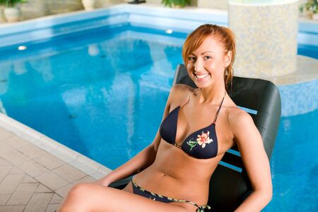 Young woman lying on deckchair by swimming pool. photo