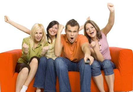 young cheering: Three young woman and a man are sitting on the orange couch and looks like watching TV. Man is holding remote control. There very excited by what theyre see. Isolated on white in studio. Stock Photo