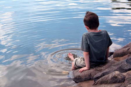 Lonely boy in thought paddles feet in lake with copy space left Stock Photo - 7741934