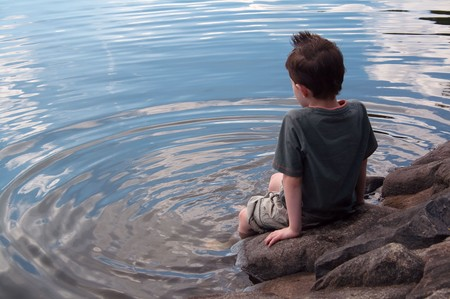 alone: Lonely boy in thought paddles feet in lake with copy space left Stock Photo
