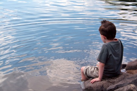 Lonely boy in thought paddles feet in lake with copy space left photo