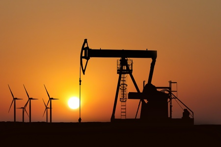 oil pump silhouette and alternative energy in a sunset background