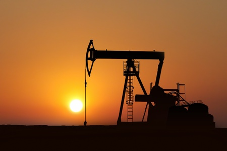 oil pump silhouette in sunset with oil tank