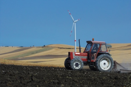 Tractor working the organic field and wind installations photo