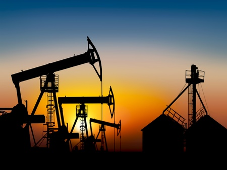 extracting petroleum in a oil field at sunset near the storage tank