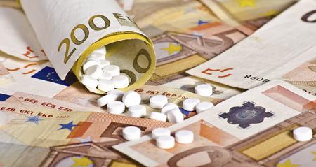 involving: Banconote europee laminati con le pillole all'interno suggerendo il costo che coinvolge medicina Archivio Fotografico