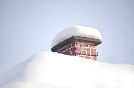 roof and chimney covered with fresh white snow in winter season